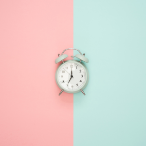 Alarm clock on pastel pink and green background