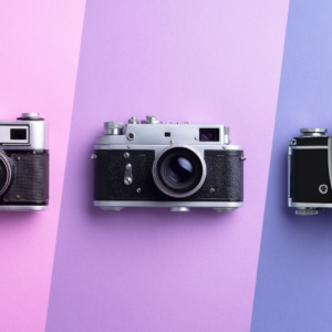 3 cameras on purple striped background
