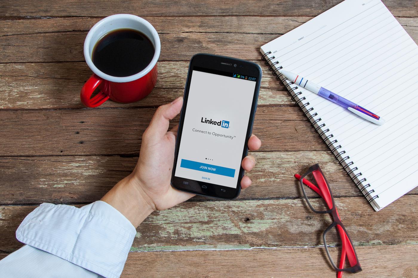 hand-holding-phone-using-linkedin