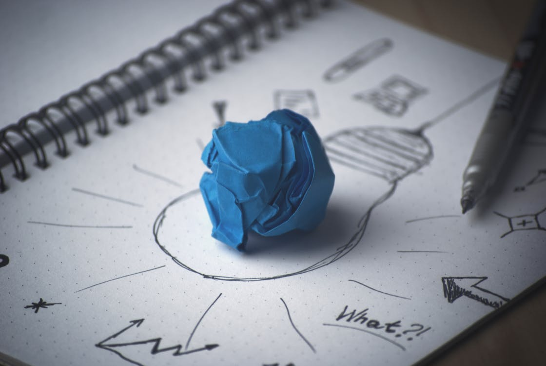 Paper with a lightbulb drawn on it with a scrunched up blue paper in the middle
