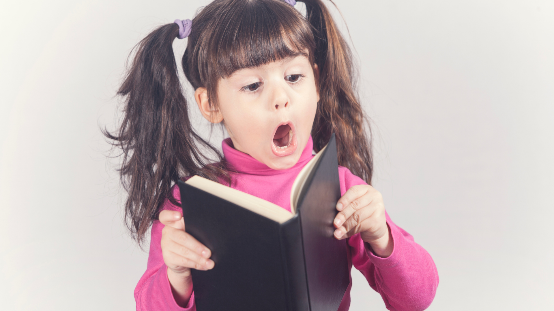 Little girl reading book looking excited
