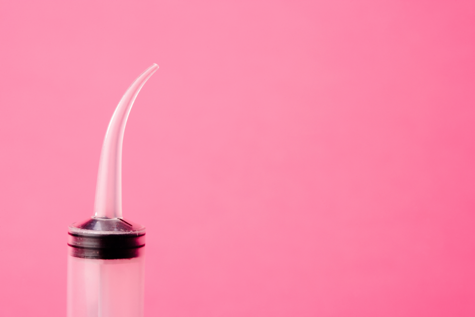 curved-syringe-pink-background